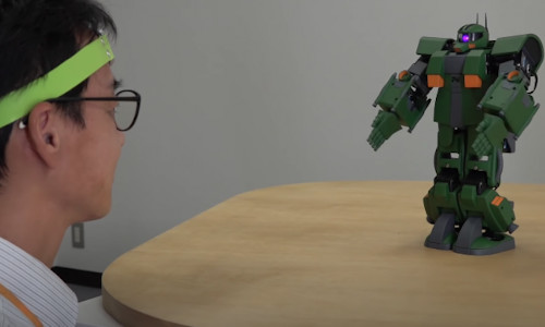 A Japanese man in front of a Gundam robot.